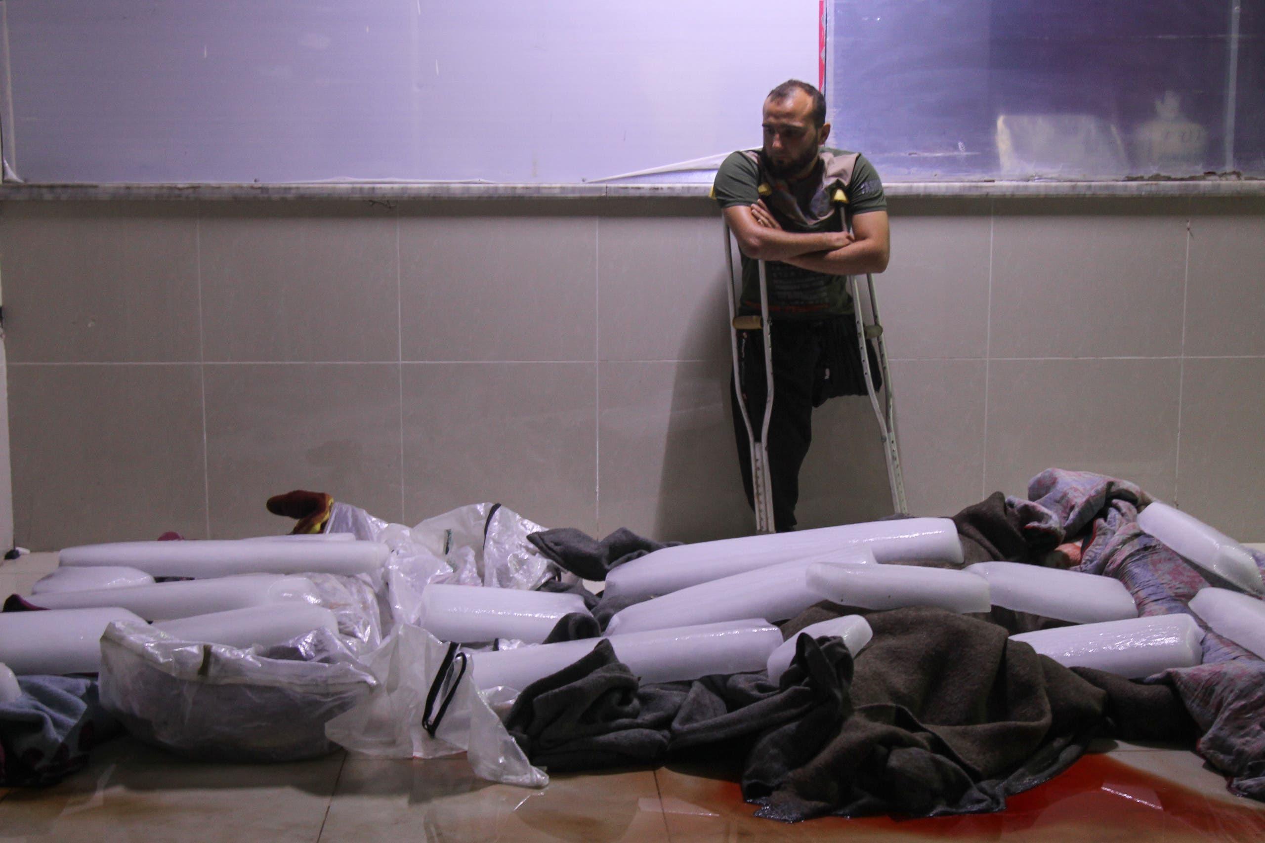 مدني يقف بجانب جثث المدنيين في إدلب