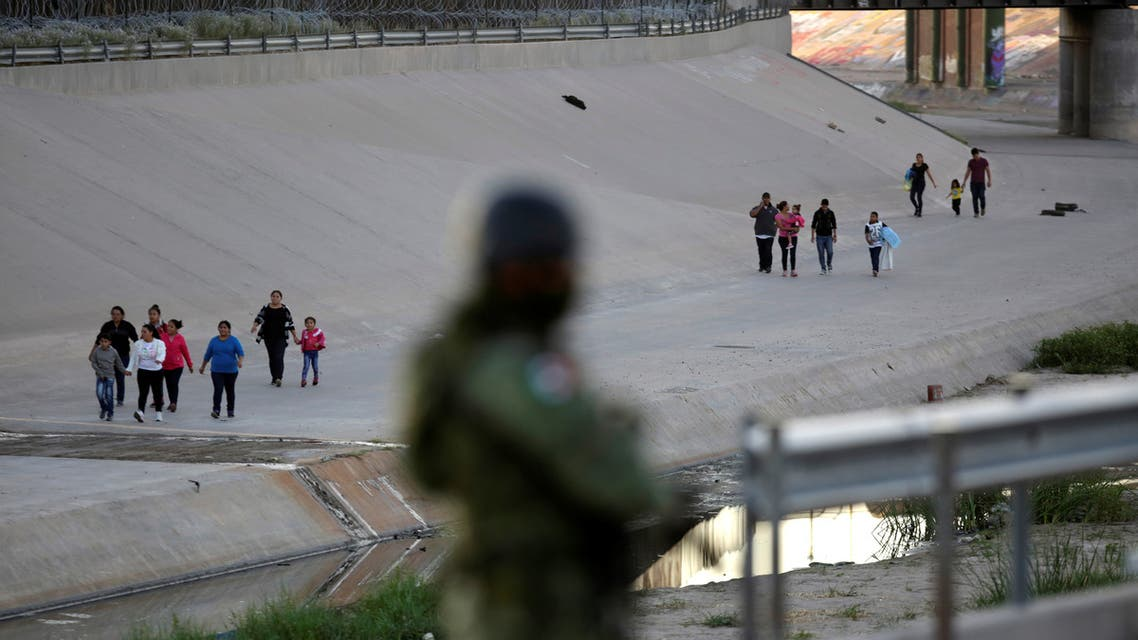 Migrants walk across the banks of the Rio Bravo after crossing illegally to the United States to turn themselves in to request asylum to U.S. Customs and Border Protection officials in El Paso, Texas, as seen from Ciudad Juarez, Mexico July 10, 2019. REUTERS/Daniel Becerril