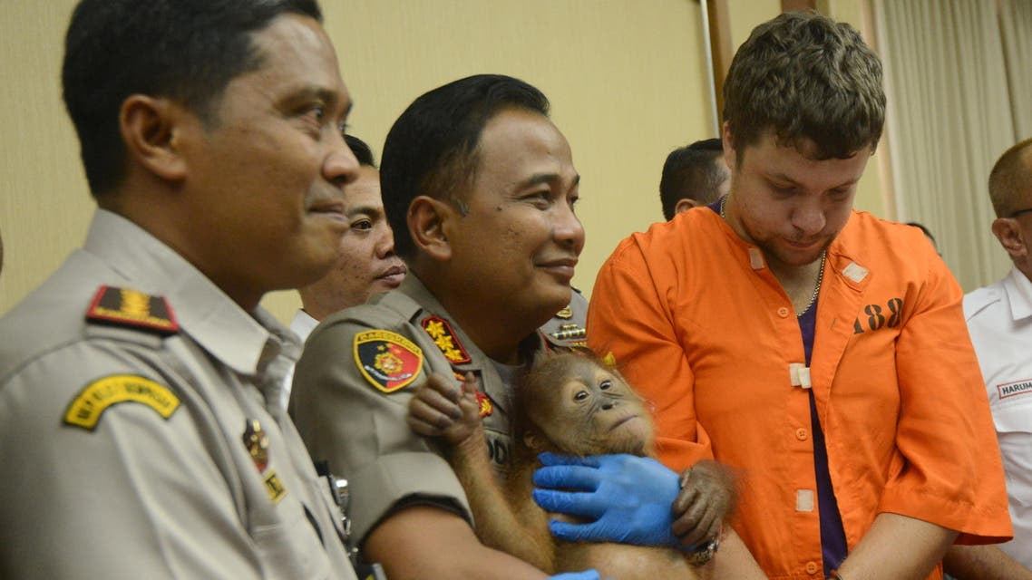 In this file photo taken on March 25, 2019 Andrei Zhestkov (R) of Russia stands near a police officer holding an orangutan during a press conference at Ngurah Rai Airport near Denpasar. (AFP)