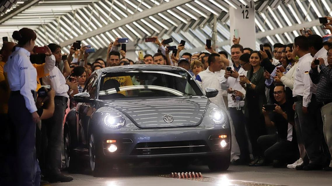 Employees take pictures of a Volkswagen Beetle car during a ceremony marking the end of production of VW Beetle cars. (Reuters)