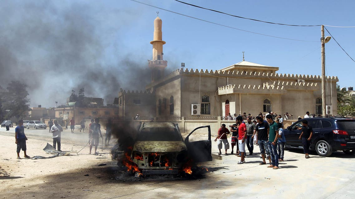 Benghazi residents and Libyan security forces gather around a burning car after an explosion killed the military prosecutor for Western Libya Youssef Ali al-Asseifar on August 29, 2013. (AFP)