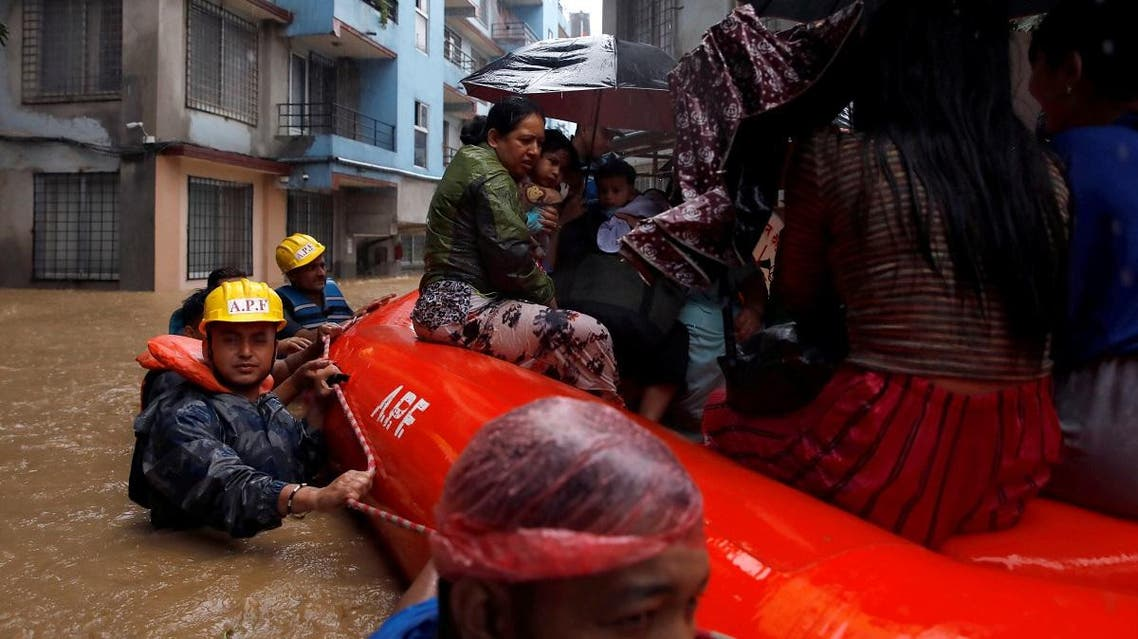 A woman carrying a child is moved by rescue workers towards dry ground from a flooded colony in Kathmandu, Nepal, on July 12, 2019. (Reuters)