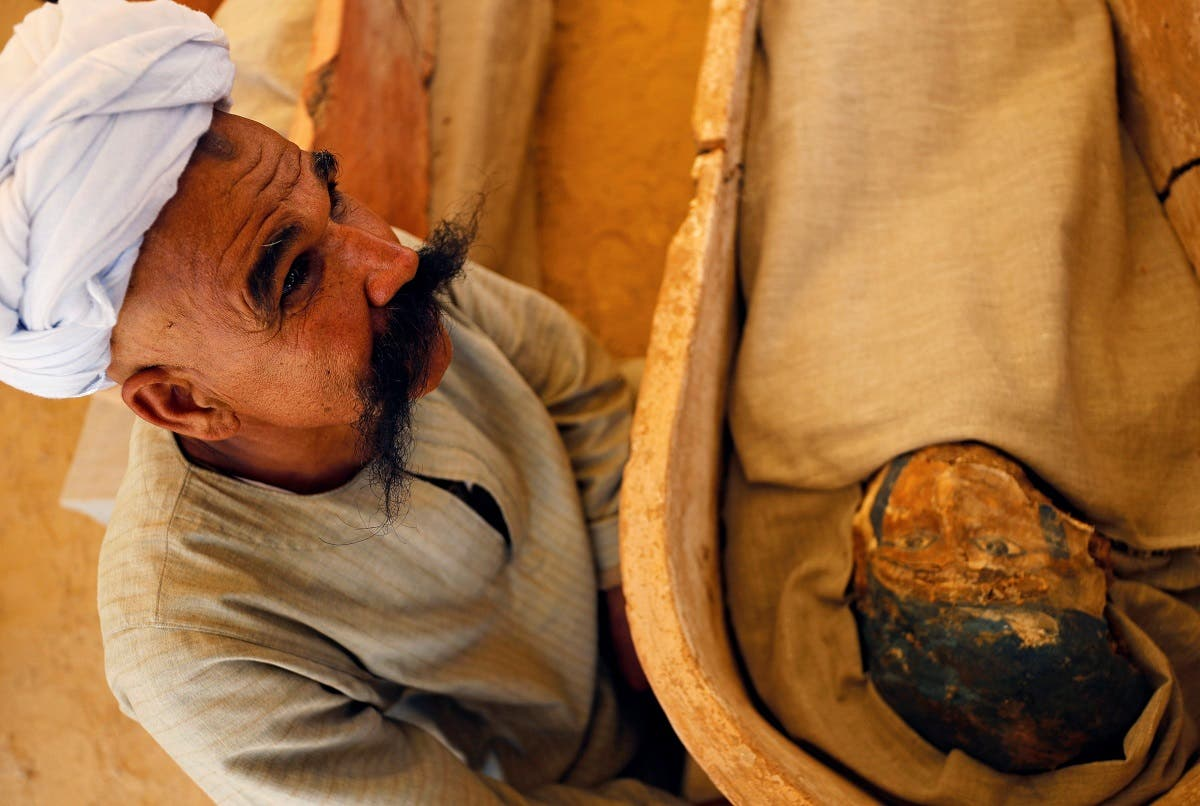 A man sits next to a mummy that was discovered near the King Amenemhat II pyramid, south of Cairo. (Reuters)
