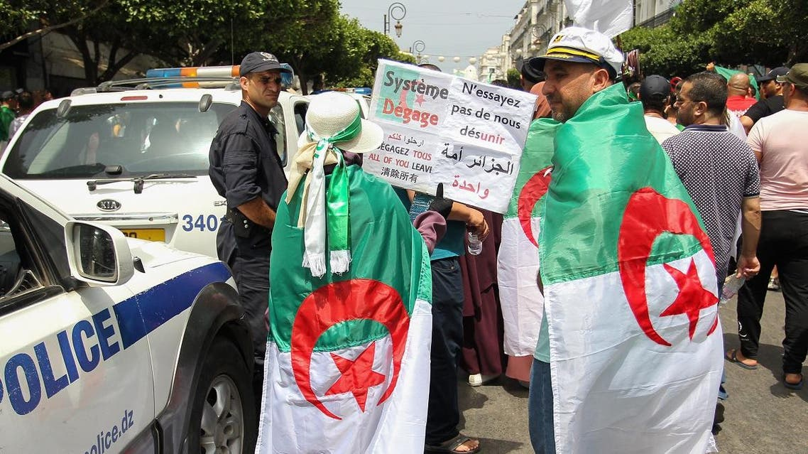 Algerian protesters, drapped in national flags, walk past a police officer during a weekly demonstration. (File photo: AFP)
