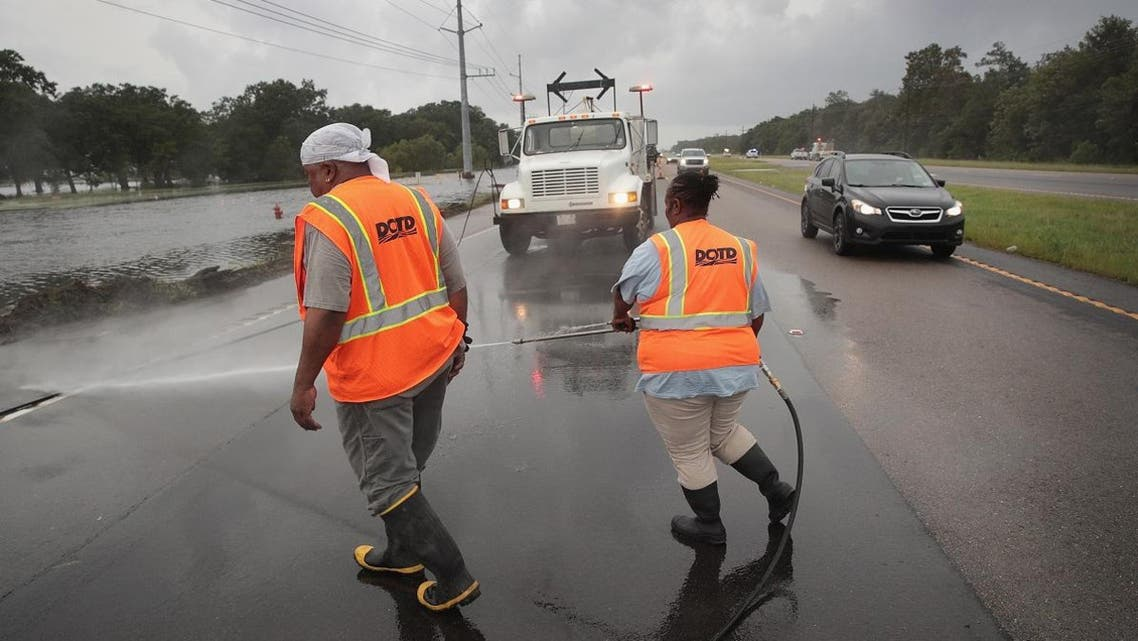 Workers clear debris left behind by Hurricane Barry on Highway 23 on July 14, 2019, near Myrtle Grove, Louisiana. (AFP)