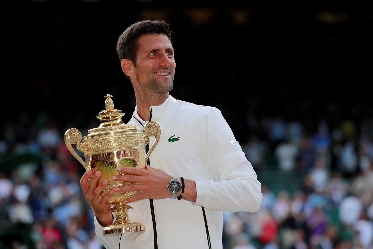 Novak Djokovic with the Wimbledon trophy as he celebrates winning the final against  Roger Federer at the All England Lawn Tennis and Croquet Club, London, on July 14, 2019. (Reuters)