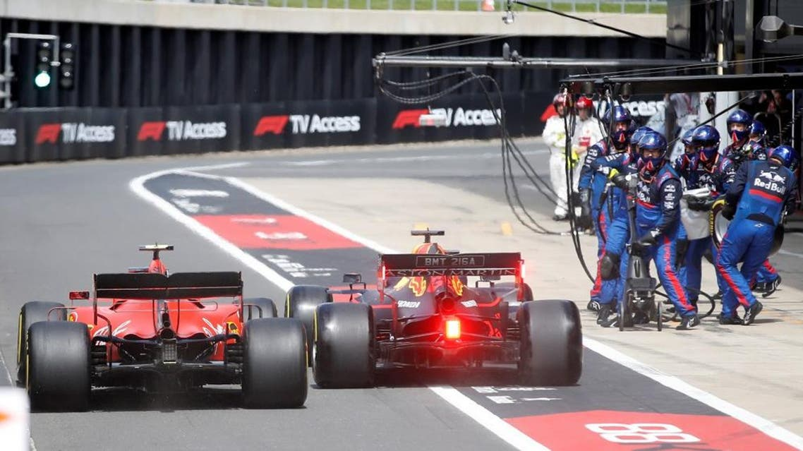 Ferrari's Monegasque driver Charles Leclerc (L) and Red Bull Racing's Dutch driver Max Verstappen (C) in the pit lane during the British Formula One Grand Prix. (AFP)