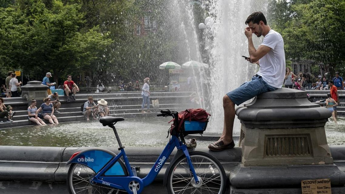 People cool off near the fountain at Washington Square Park during a hot afternoon day. (AFP)
