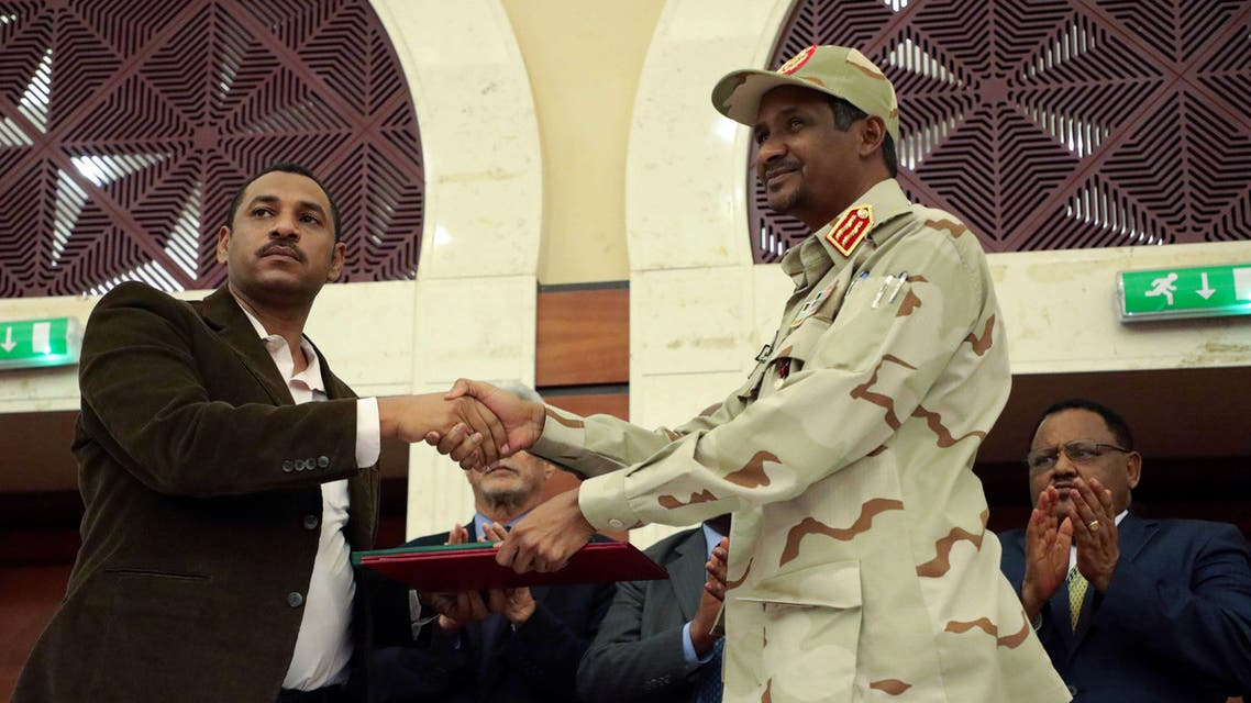 REFILE - REMOVING RESTRICTION Deputy Head of Sudanese Transitional Military Council, Mohamed Hamdan Dagalo and opposition alliance signed coalition's leader Ahmad al-Rabiah shake hands after signing a political accord as part of a power-sharing deal aimed at leading the country to democracy following three decades of autocratic rule in Khartoum, Sudan July 17, 2019. REUTERS/Stringer