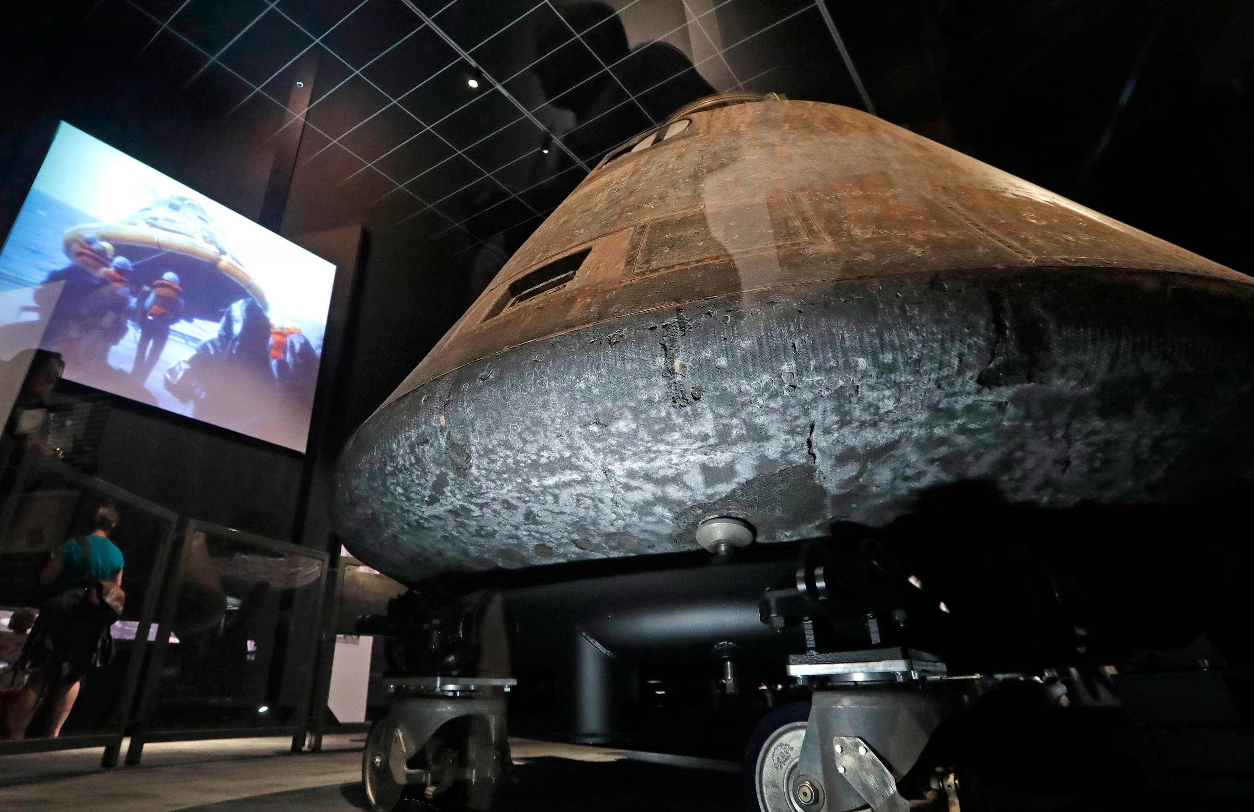 The NASA Apollo 11 command module Columbia, its bottom scorched and pitted from reentry into Earth's atmosphere decades earlier, is displayed at the centerpiece of an Apollo 11 mission exhibit at the Museum of Flight in Seattle. (AP)