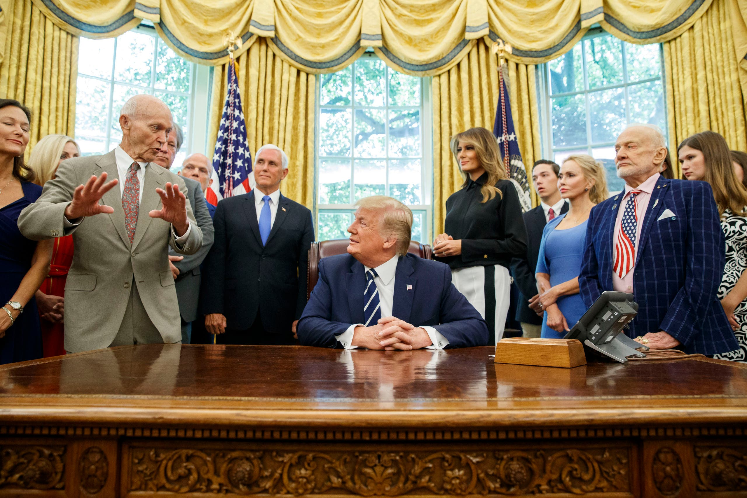 President Donald Trump, accompanied by Apollo 11 astronauts Michael Collins, left, and Buzz Aldrin, with Vice President Mike Pence and first lady Melania Trump, listens during a photo opportunity commemorating the 50th anniversary of the Apollo 11 moon landing, in the Oval Office of the White House. (AP)