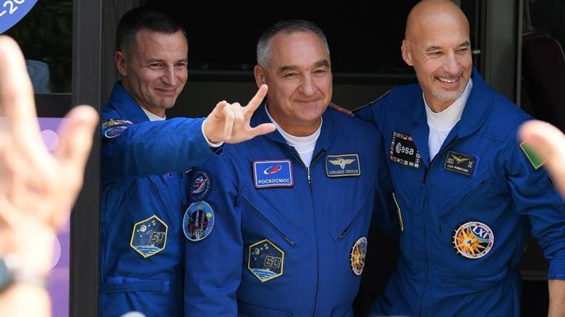 Members of the International Space Station (ISS) expedition 60/61, Andrew Morgan, Alexander Skvortsov and Luca Parmitano pose by a bus during a farewell ceremony on July 20, 2019. (AFP)