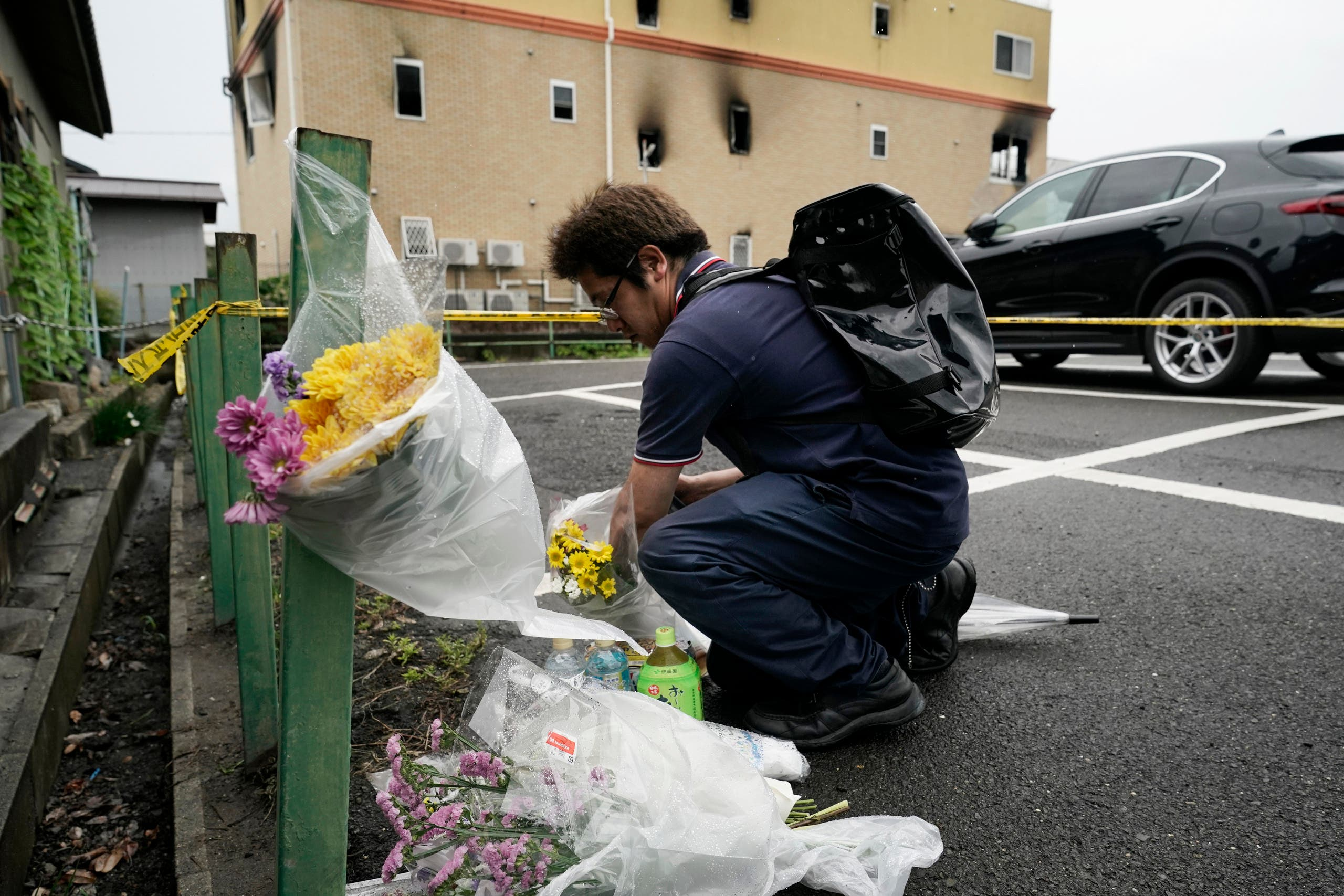 A man places flowers outside the Kyoto Animation Studio building consumed in an arson attack in Kyoto, Japan. (AP)