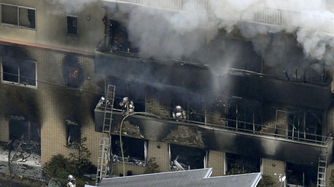 An aerial view shows firefighters battling the fires at the site where a man started a fire after spraying a liquid, at a three-story studio of Kyoto Animation Co. in Kyoto, western Japan (Reuters)