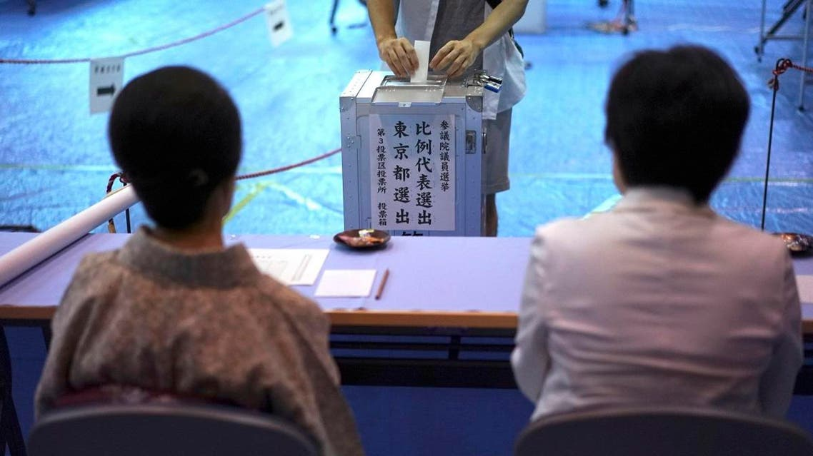 A voter casts a ballot in the upper house elections as representatives of a local election administration commission observe at a polling station in Tokyo. (AP)