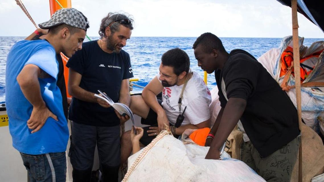 A handout photo released on September 25, 2018 by SOS Mediterranee shows rescued migrants talking with crew members at the Aquarius rescue ship. (AFP)