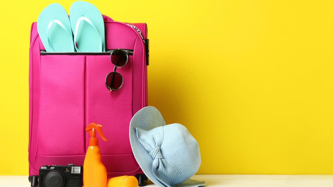 Pink suitcase with flip-flops, hat, sunglasses and sunscreen bottles on wooden table stock photo