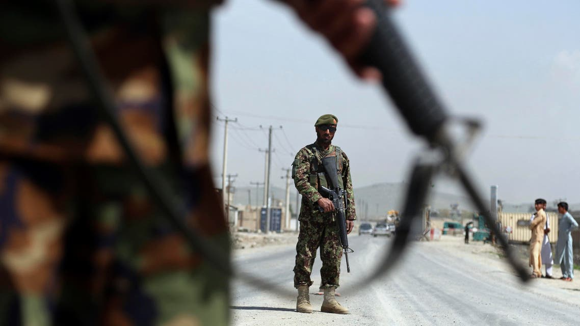 in this Sunday, April 28, 2019 photo, Afghan National Army soldiers stand guard at a checkpoint on the Jalalabad-Kabul road, on the outskirts of Kabul, Afghanistan. (AP)