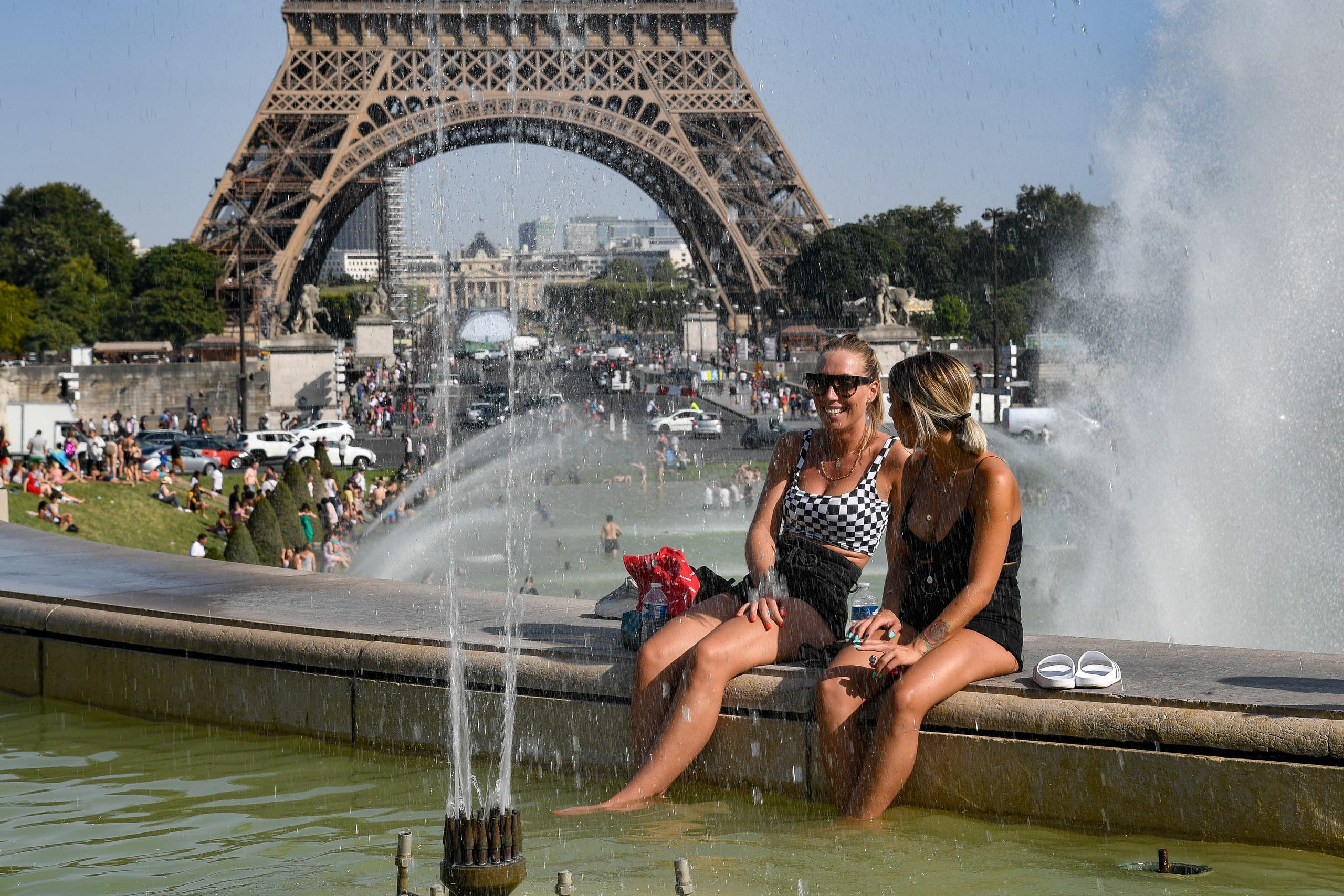 Women cool off at the Trocadero Fountains next to the Eiffel Tower in Paris as a new heatwave hits Europe. (AFP)