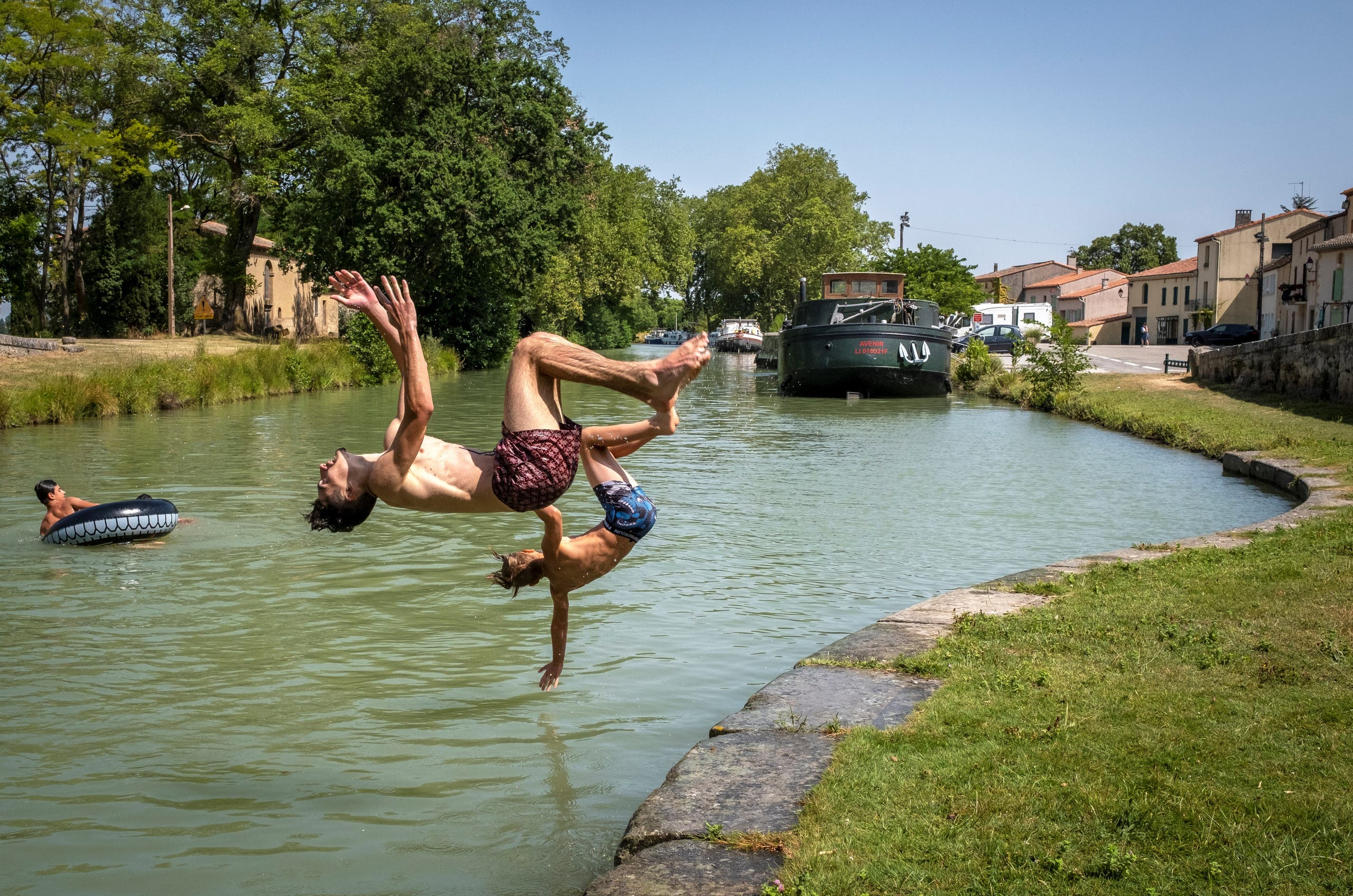 Young men dive into the Canal du Midi at the Port du Segala in Labastide d'Anjou on July 23, 2019 as a new heatwave blasted into northern Europe that could set records in several countries. (AFP)
