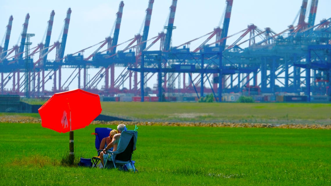 People take a sunbath as in background can be seen facilities of a North Sea container port on July 24, 2019 in Wremen, northwestern Germany, where temperatures reached 34 degrees Celsius. (AFP)