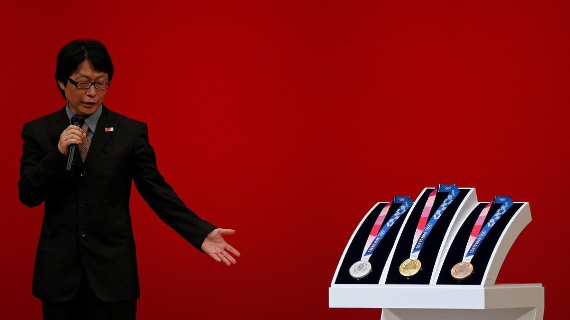 Medal designer Junichi Kawanishi speaks next to the design of the Tokyo 2020 Olympic medals. (Reuters)