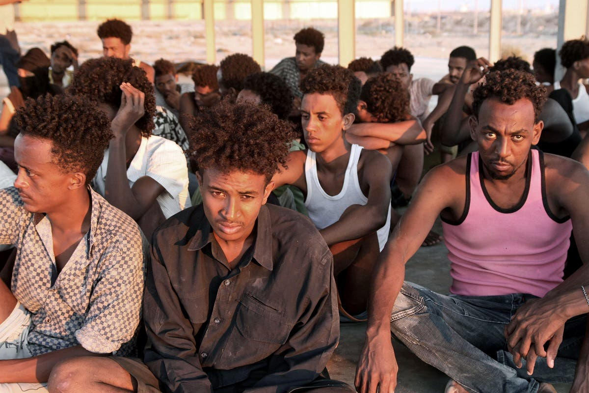 Rescued migrants sit on the coast of Khoms, some 100 kilometers from the Libyan capital Tripoli, on July 26, 2019. (File photo: AFP)