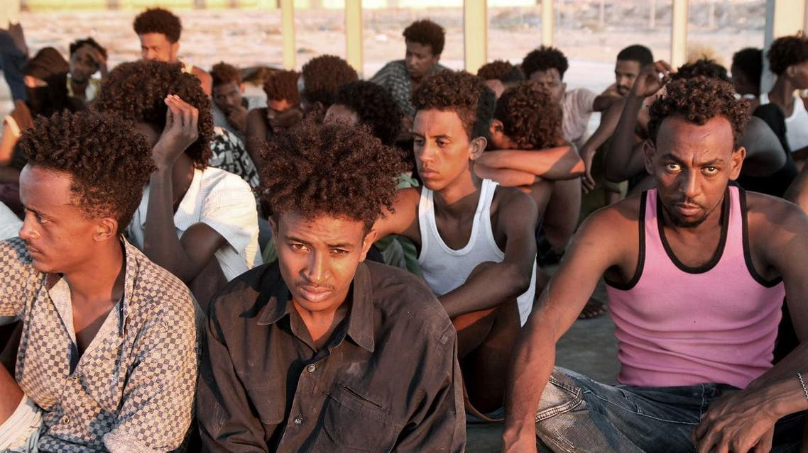 Rescued migrants sit on the coast of Khoms, some 100 kilometers from the Libyan capital Tripoli, on July 26, 2019. (AFP)