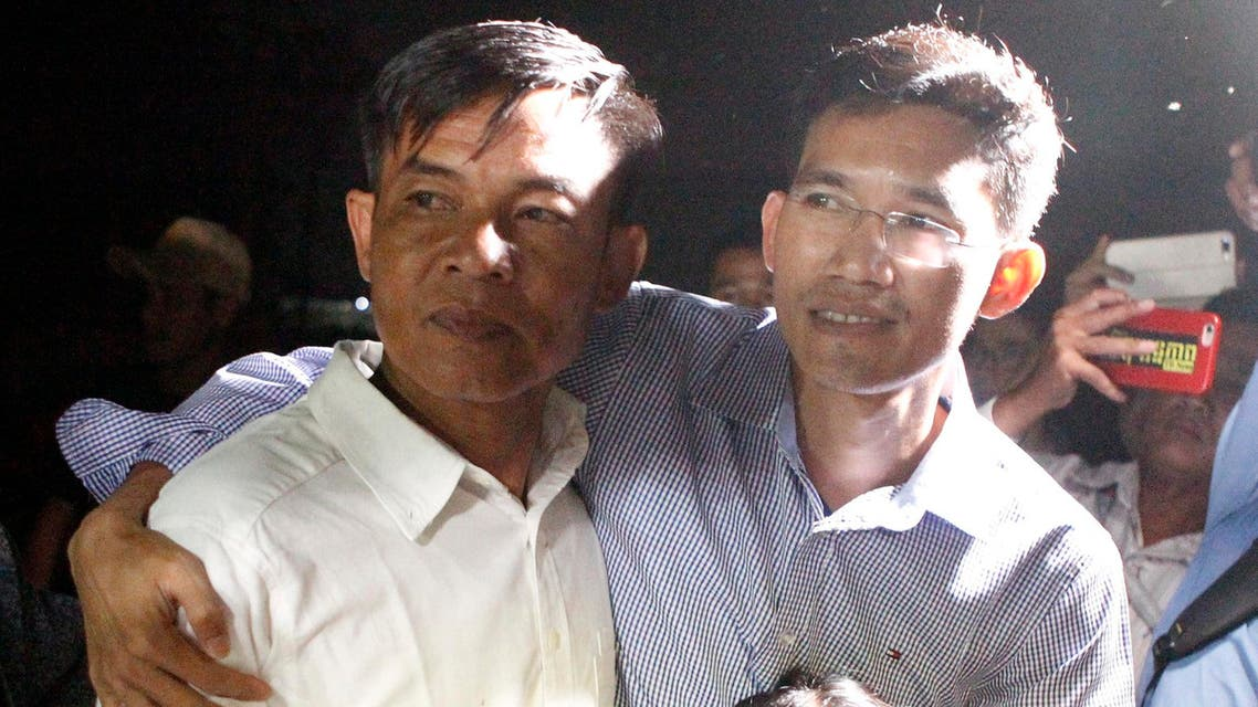 Two former Radio Free Asia reporters Uon Chhin, left, and Yeang Socheamet, right, hold together after they walk outside the main prison of Prey Sar at the outskirt of Phnom Penh, Cambodia (AP)