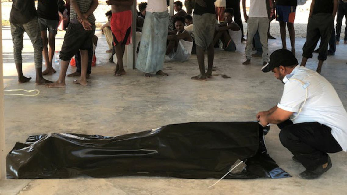 Migrants watch the body of their fellow migrant who died after a wooden boat capsized off the coast of Komas, a town east of the capital Tripoli