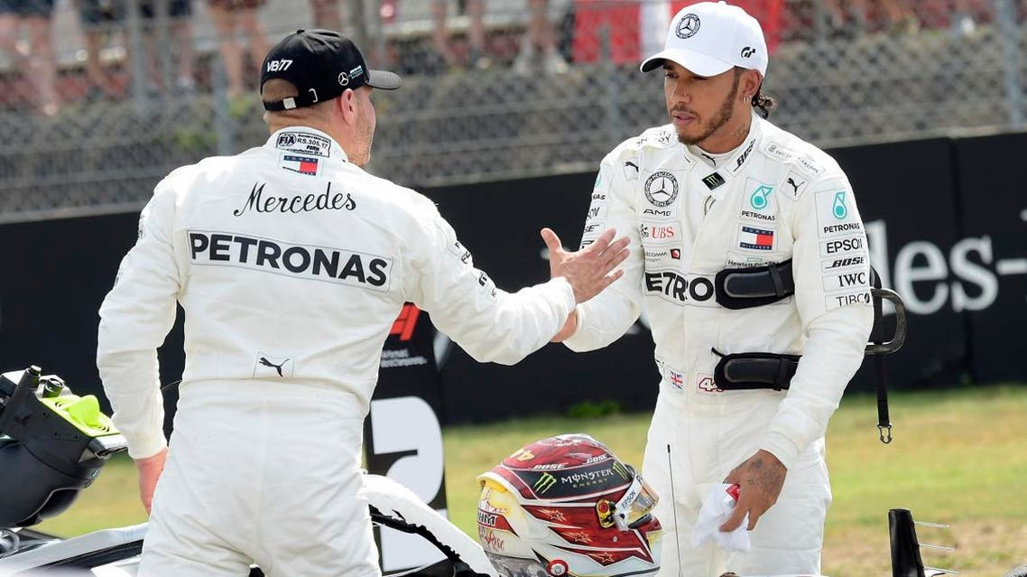 Lewis Hamilton celebrates after he clocked the fastest time as he shakes hands with third fastest time Valtteri Bottas after the qualifying session at the Hockenheimring racetrack in Germany on, July 27, 2019. (AP)