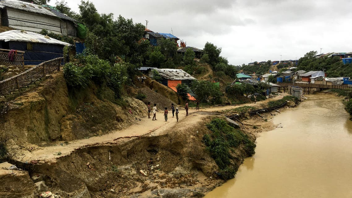 Rohingya children walk around a landslide area at Balukhali refugee camp in Ukhia on July 7, 2019. (AFP)