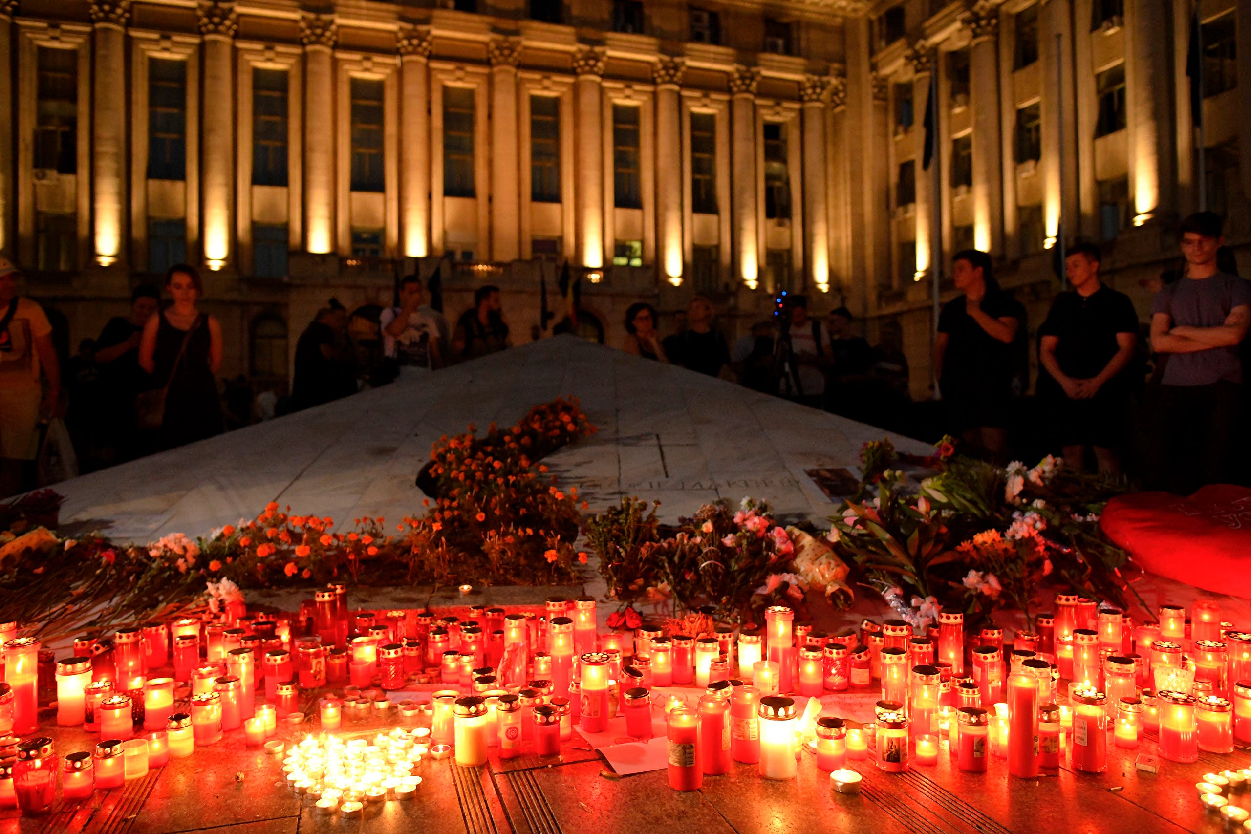 Candles are lit outside the interior ministry building in memory of a 15-year-old girl, raped and killed in southern Romania, after police took 19 hours from the moment she called the country's emergency hotline to intervene. (AP)
