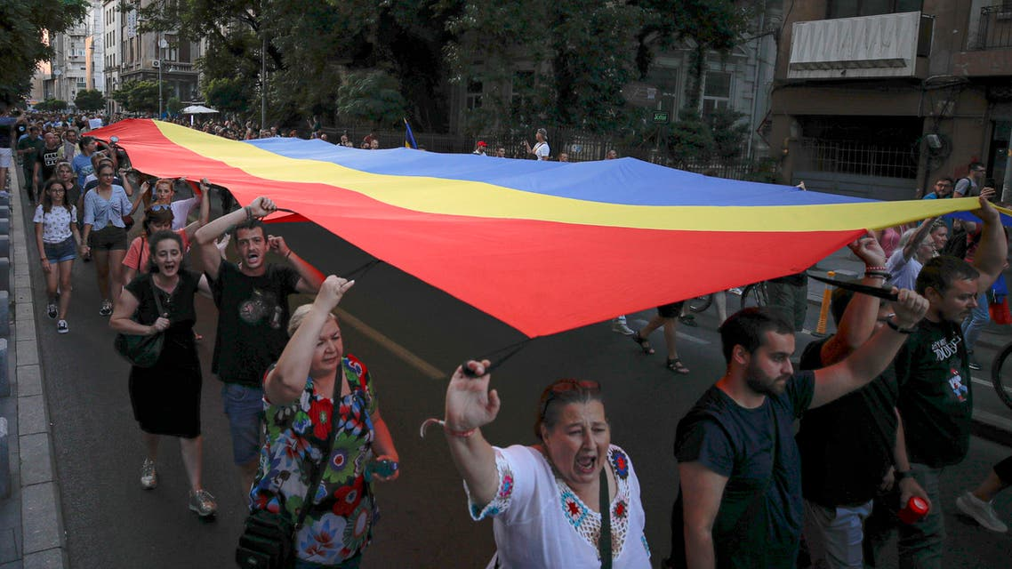 People hold a large Romanian flag while marching from the government headquarters in memory of a 15-year-old girl, raped and killed in southern Romania (AP)