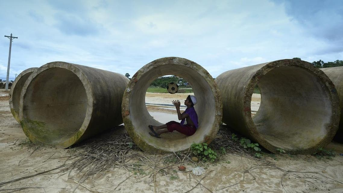 A Rohingya child plays with a football inside a sewage pipe at Kutupalong refugee camp in Ukhia on July 24, 2019. (AFP)