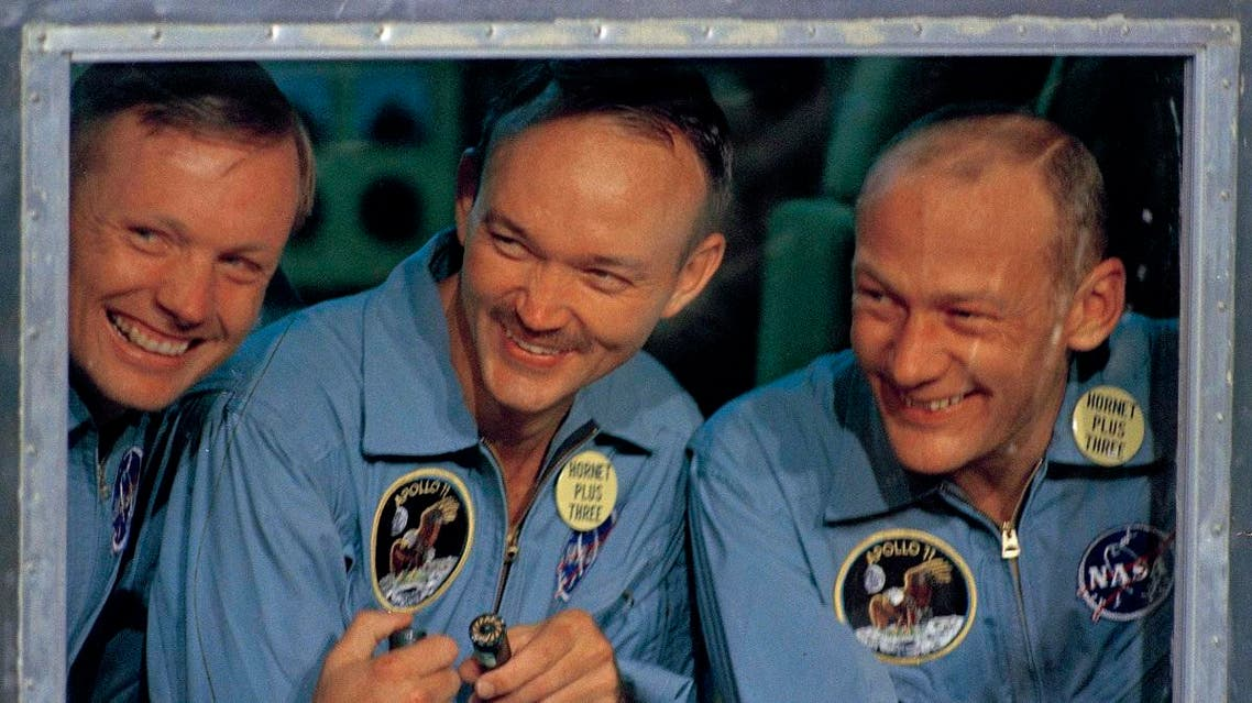 """In this July 24, 1969, file photo, Apollo 11 astronauts, Neil Armstrong, (left), Michael Collins, (center), and Edwin """"Buzz"""" Aldrin smile as they answer questions from quarantine in an isolation unit aboard the USS Hornet after splashdown and recovery. (AP)"""