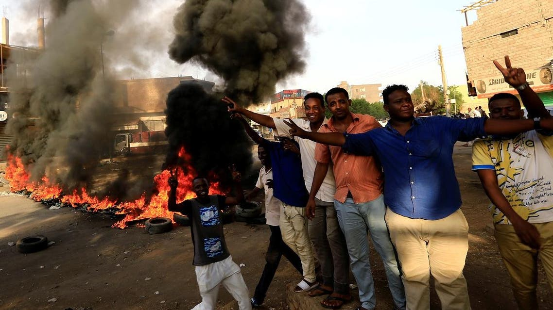 Protesters chant slogans and burn tyres during a demonstration against a report of the Attorney-General on the dissolution of the sit-in protest in Khartoum. (Reuters)