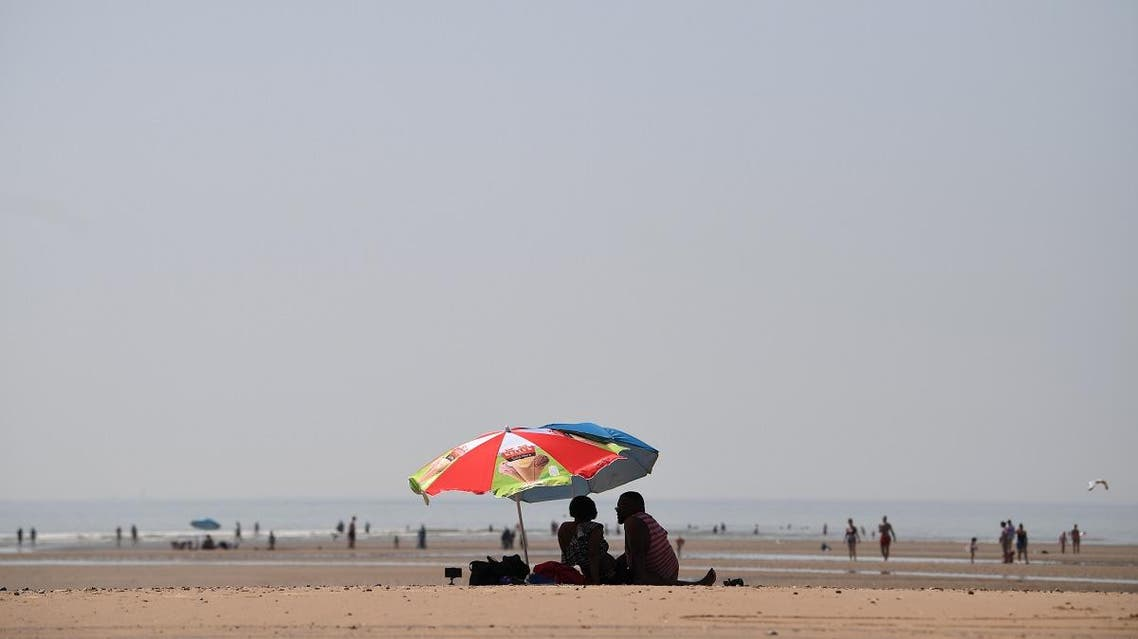 Beach-goers shelter under an umbrella by the sea in Camber Sands, southern England. (AFP)