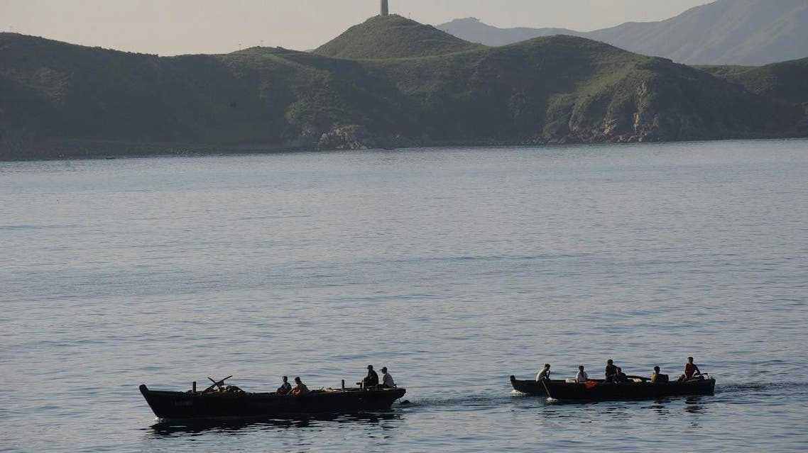 This picture taken on August 31, 2011 shows fishermen going out in their boats as the cruise ship Mangyongbong prepares to dock at Mount Kumgang port in the first-ever cruise from Rason in North Korea. (AFP)