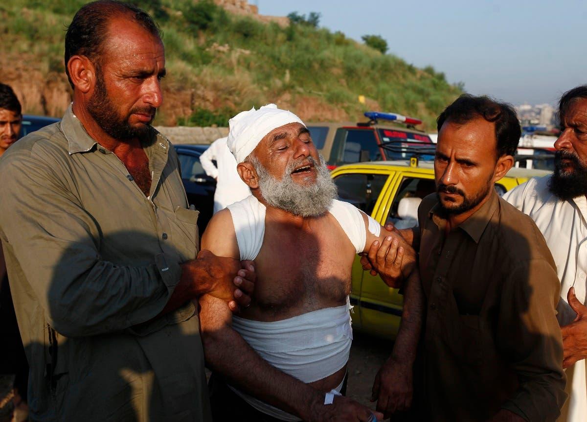 People help an injured man after a Pakistan army plane crash in Rawalpindi, Pakistan, Tuesday, July 30, 2019. (AP)