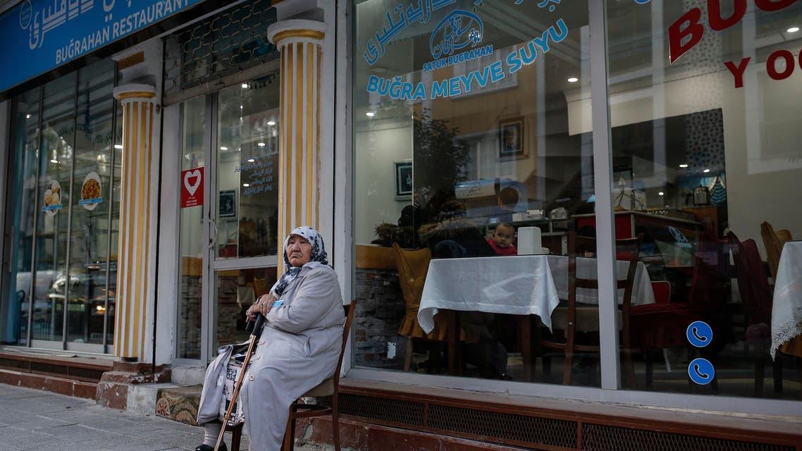 In this photo taken Thursday, Dec. 14, 2017, a Uighur woman sits outside a shop in the Uighur immigrant neighborhood of Zeytinburnu. (AP)