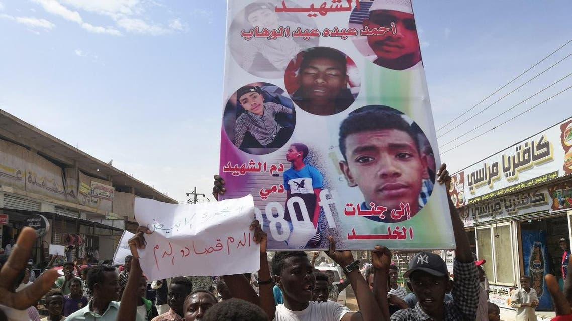 Sudanese protesters march with a poster bearing the portraits of victims, who were shot dead for protesting against a shortage of bread, during a demonstration in the central city of al-Obeid on July 31, 2019. (AFP)