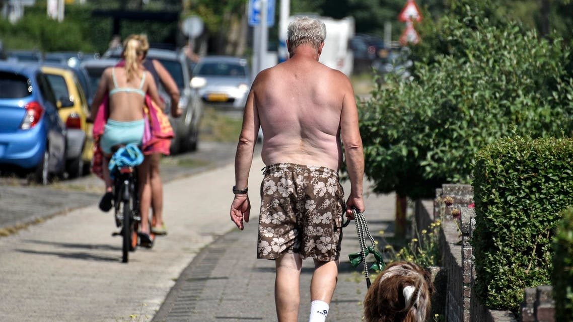 A man and his dog walk without a shirt in the summer heat on Thursday, July 25, 2019 in the city of Egmond, northern Netherlands. (AP)