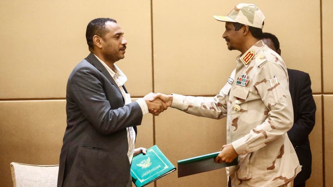 General Mohamed Hamdan Daglo (R), Sudan's deputy head of the Transitional Military Council, and protest leader Ahmed Rabie shake hands after signing the constitutional declaration. (AFP)