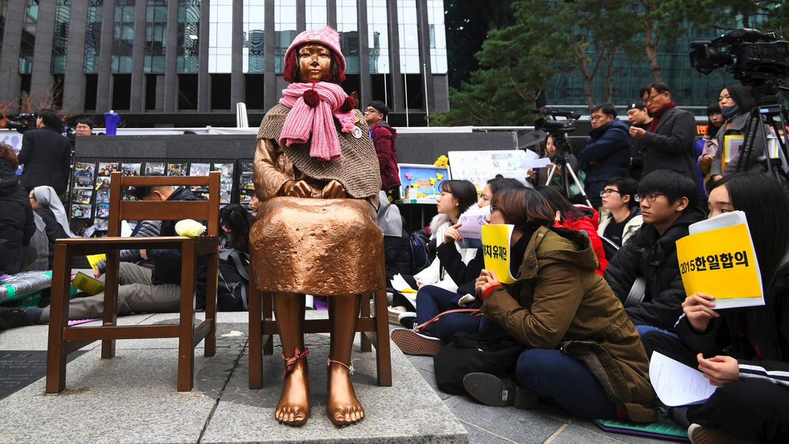 """South Korean protesters sit near a statue of a teenage girl symbolizing former """"comfort women"""", who served as sex slaves for Japanese soldiers during World War II, during a weekly anti-Japanese demonstration in front of the Japanese embassy in Seoul on November 21, 2018. (AFP)"""