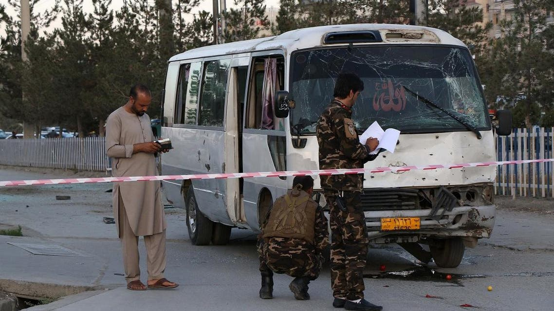 Afghan security personnel investigate a damage bus carrying employees of Khurshid TV, at the site of a sticky bomb blast in Kabul on August 4, 2019. (AFP)