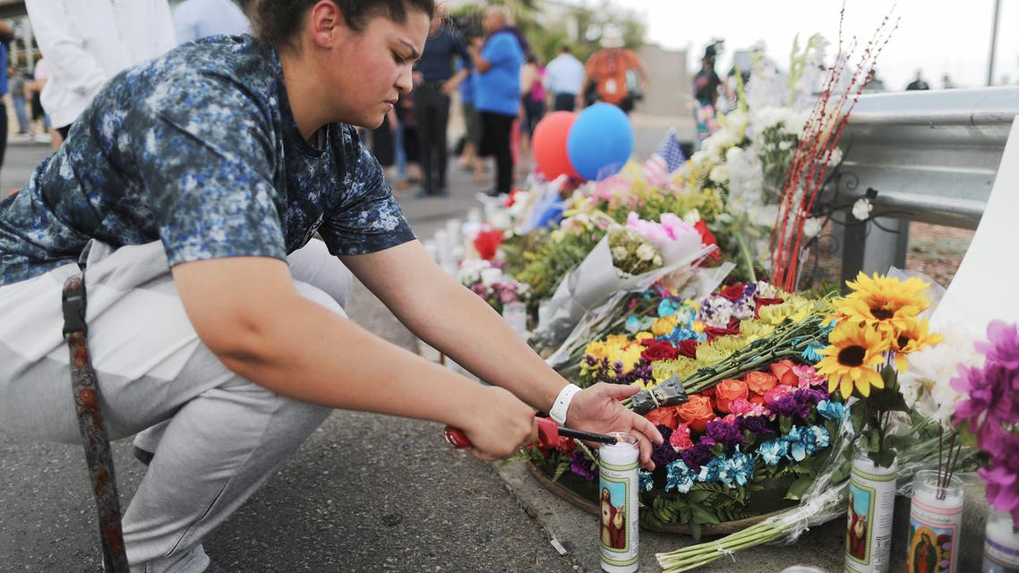 EL PASO, TEXAS - AUGUST 04: A woman lights a candle at a makeshift memorial outside Walmart, near the scene of a mass shooting which left at least 20 people dead, on August 4, 2019 in El Paso, Texas. A 21-year-old male suspect was taken into custody in the city which sits along the U.S.-Mexico border. At least 26 people were wounded. Mario Tama/Getty Images/AFP