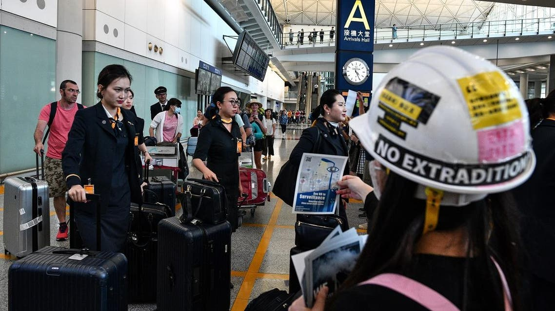 Cabin crew walk past a protester handing out leaflets and chanting slogans as protesters rally against a controversial extradition bill in the arrivals hall of the international airport in Hong Kong on July 26, 2019. (AFP)