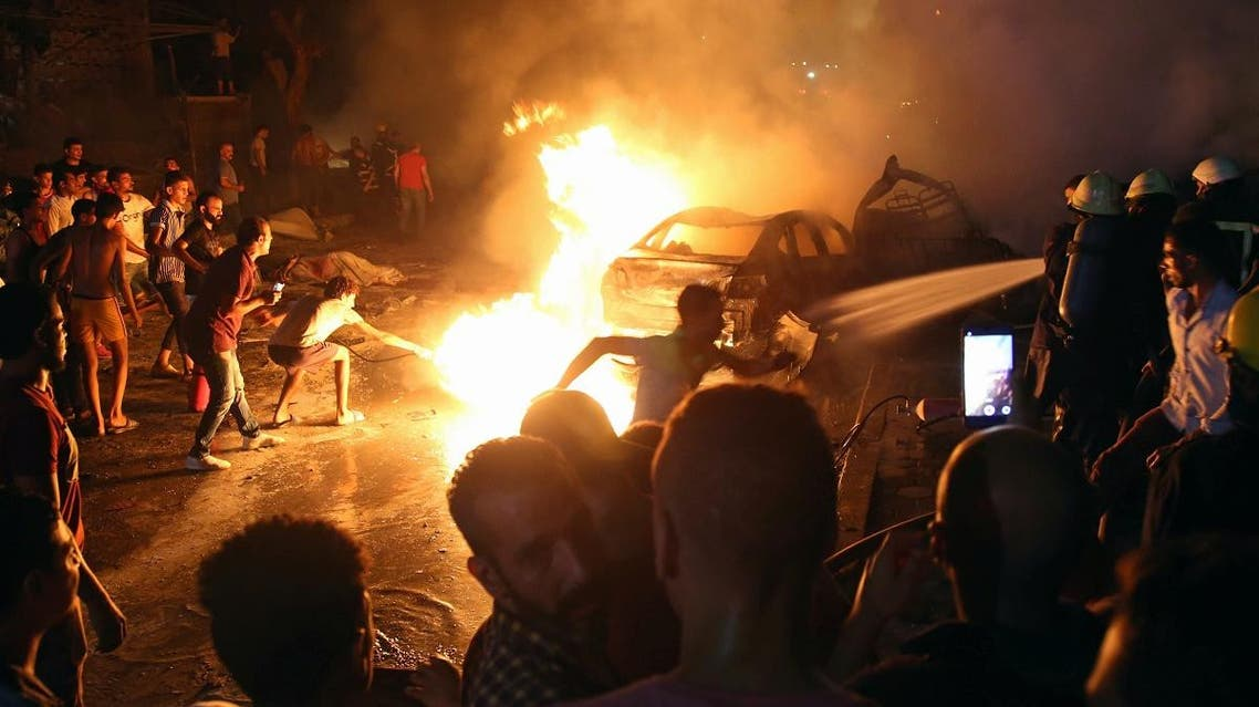 People extinguish a fire from a blast outside the National Cancer Institute, Cairo. (Reuters)