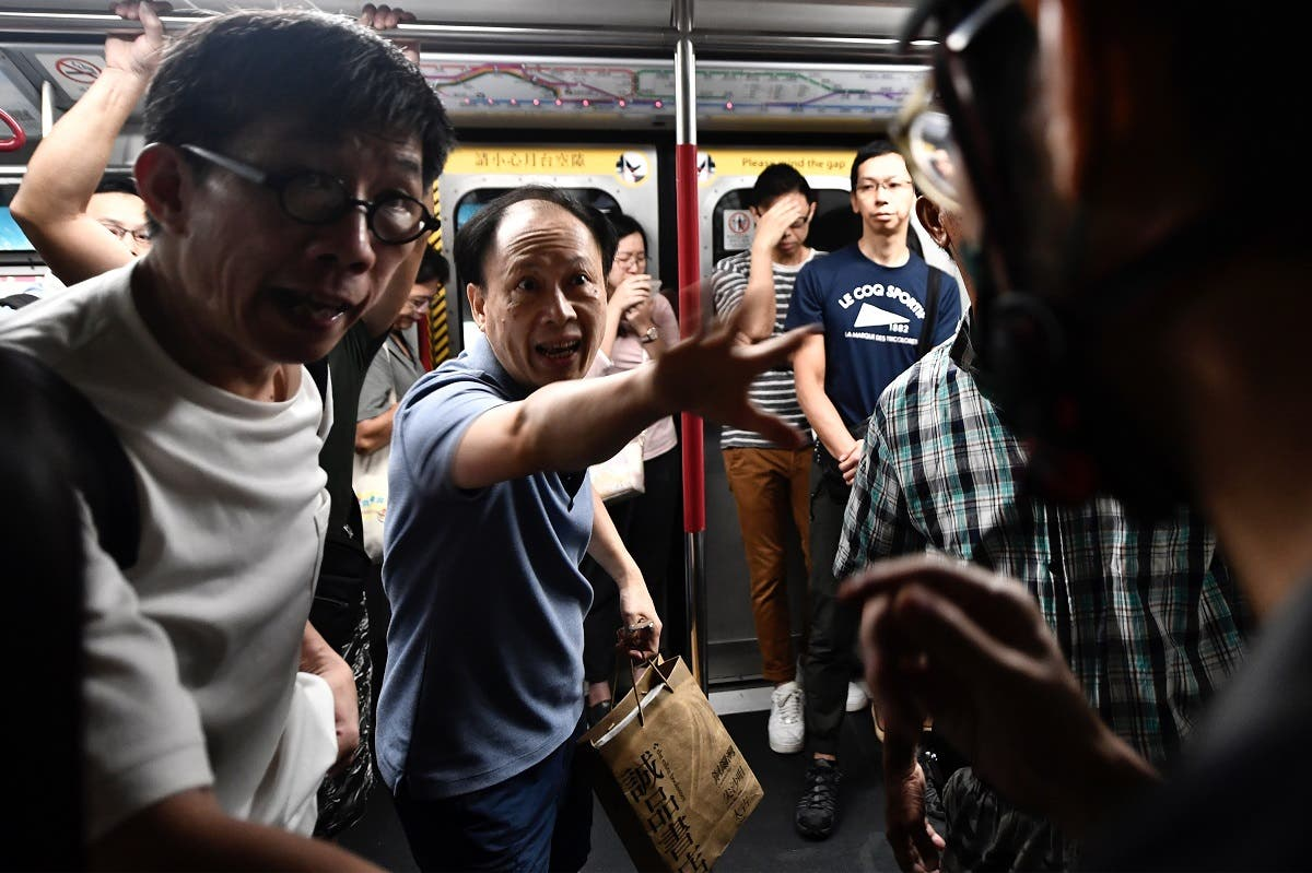 A passenger gestures towards a protester (R) after he prevented the doors of a MTR underground train from closing at Fortress Hill station during morning disruptions to the rush hour commute in Hong Kong on August 5, 2019. (AFP)